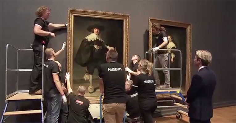 Medewerkers van het Rijksmuseum Amsterdam hangen de huwelijksportretten van Marten en Oopjen aan de muur.