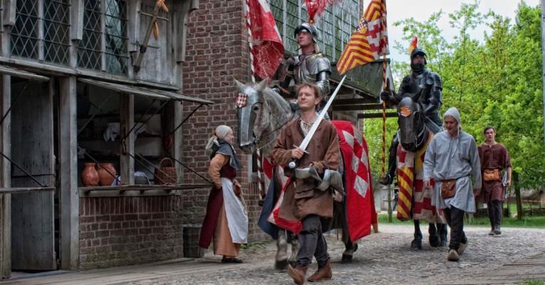 Een optocht in het Archeon. Voorop een ridder op zijn paard en een vaandeldrager.